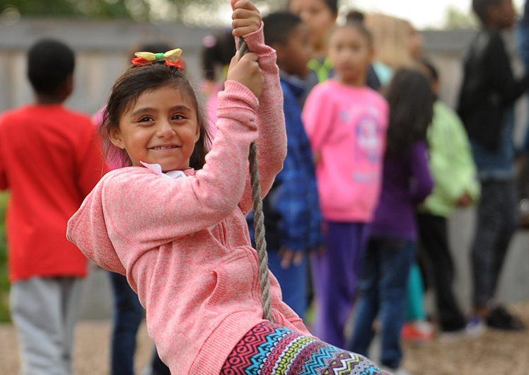 Little girl swinging on rope