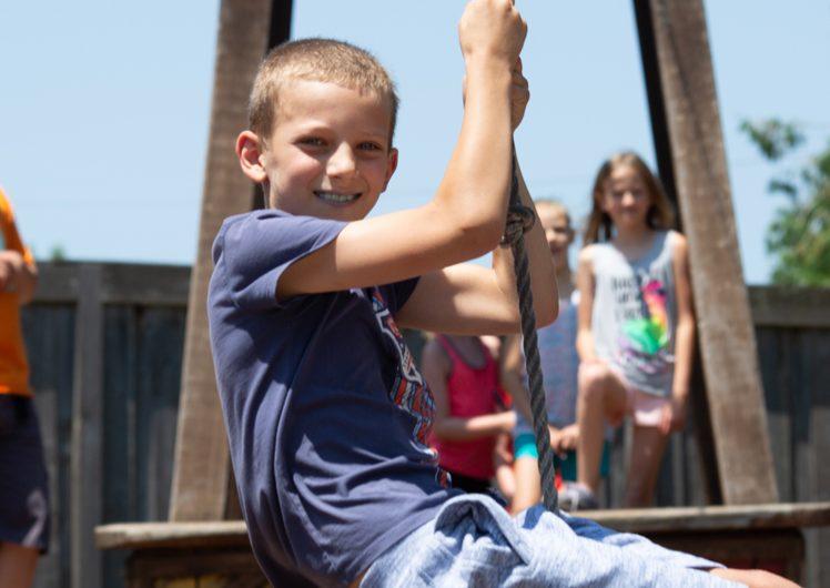 Boy swinging on rope at playground