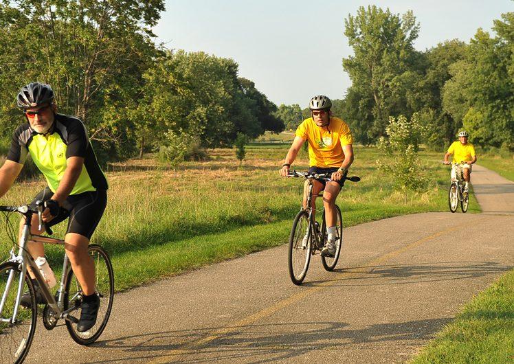 Three men biking along trail on sunny day